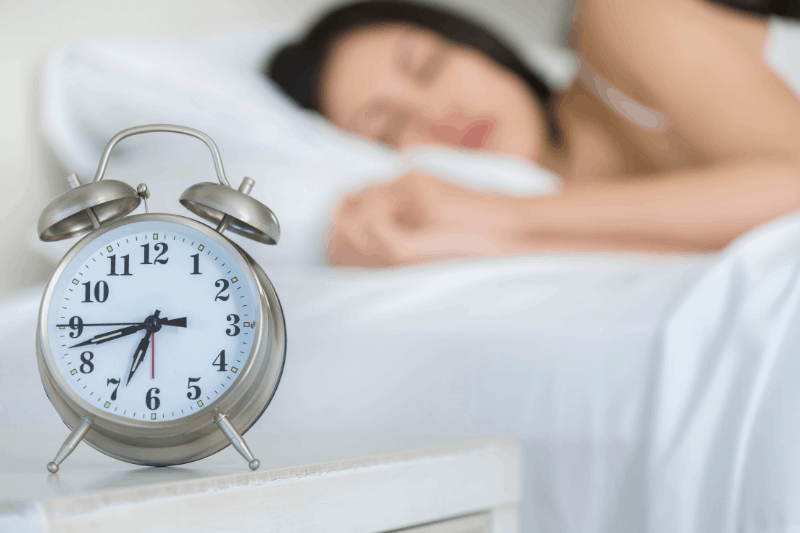 woman sleeping in bed in background, alarm clock in the foreground