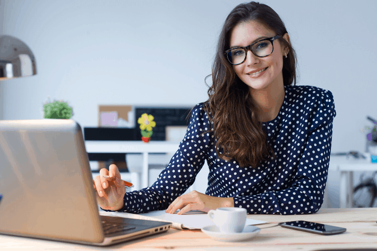 smiling woman sitting at desk with laptop and cup of coffee